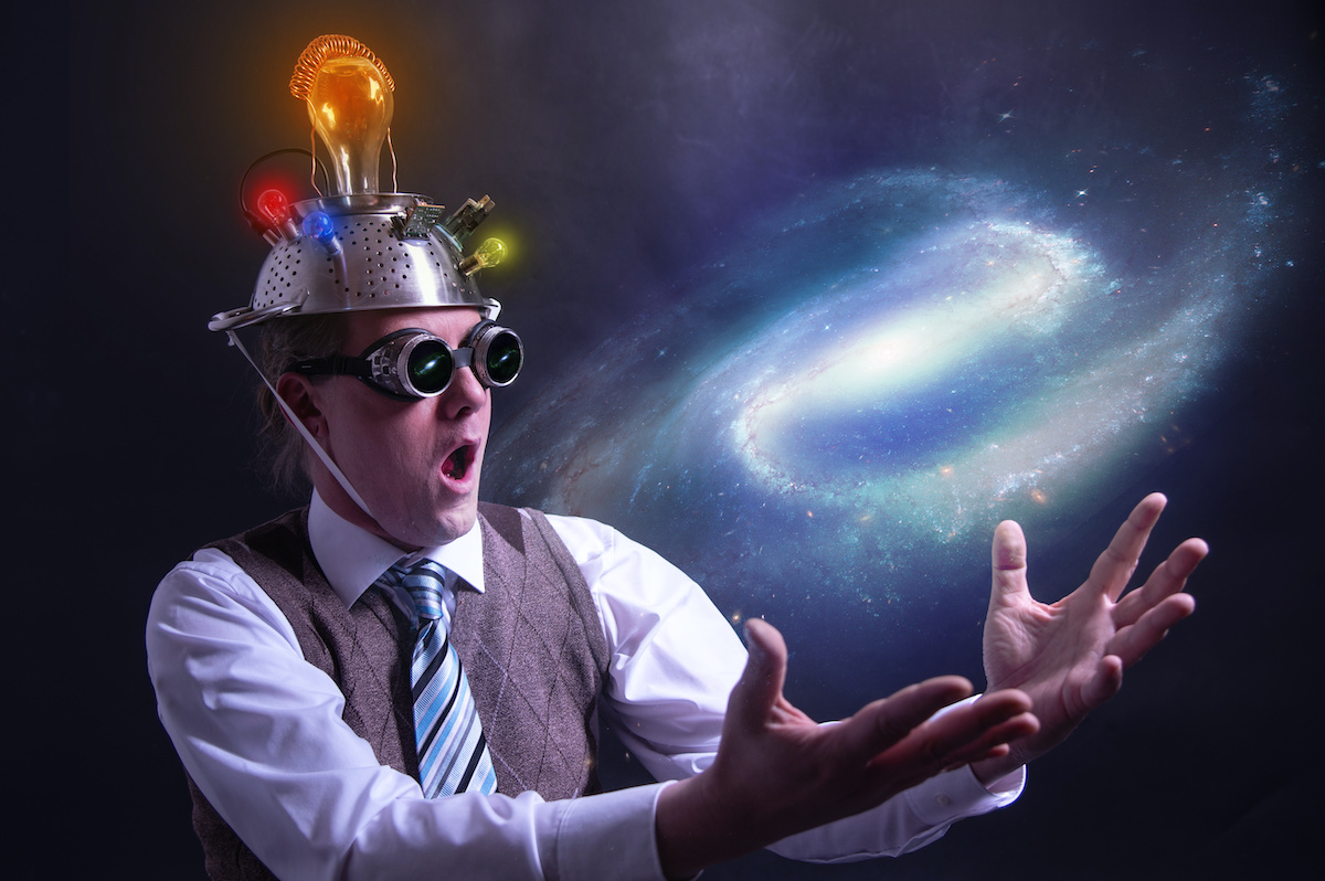 distraught looking conspiracy believer in suit with aluminum foil head holding the galaxy or universe in his hands - nerd